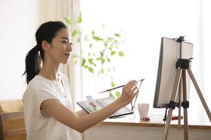 室内で筆を持ち絵を描く女性の写真素材 [FYI04102301]