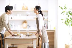 テーブルを挟んで会話する夫婦の写真素材 [FYI04102495]