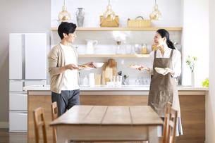 キッチンから食事を運ぶ夫婦の写真素材 [FYI04102496]