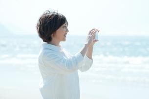 スマホで写真を撮る女性の写真素材 [FYI04102498]