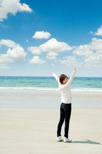 綺麗な海の波打ち際で振り返りながら笑う女性の写真素材 [FYI04102499]