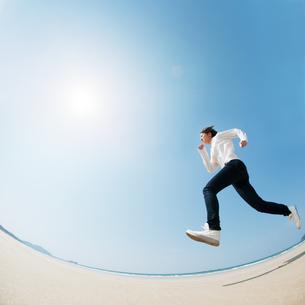 砂浜でジャンプする女性の写真素材 [FYI04102501]