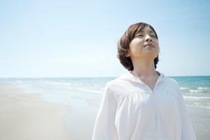 波打ち際でリラックスする女性の写真素材 [FYI04102507]