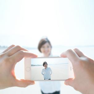 スマホで写真を撮られる女性の写真素材 [FYI04102509]