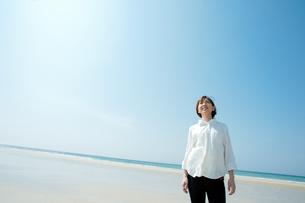 綺麗な海で空を見上げる女性の写真素材 [FYI04102510]