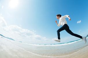 砂浜でジャンプする女性の写真素材 [FYI04102512]