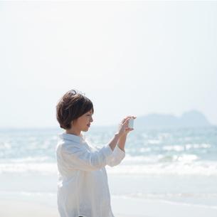 スマホで写真を撮る女性の写真素材 [FYI04102517]