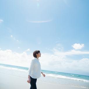 波打ち際を歩く女性の写真素材 [FYI04102527]