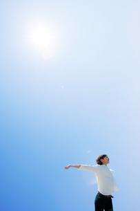 日差しを浴びて伸びをする女性の写真素材 [FYI04102528]