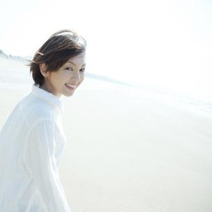 砂浜を走りながら振り返る女性 の写真素材 [FYI04102532]