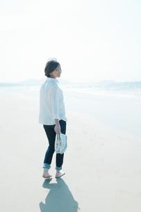 砂浜を靴を持って裸足で歩く女性の写真素材 [FYI04102533]