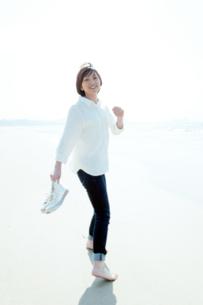 砂浜を靴を持って裸足で歩く女性の写真素材 [FYI04102534]