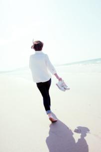 砂浜を靴を持って裸足で歩く女性の後ろ姿の写真素材 [FYI04102535]