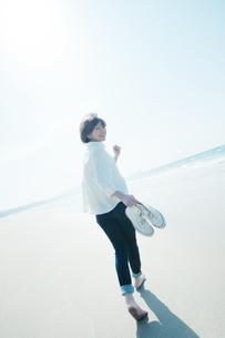 砂浜を靴を持って裸足で走る女性の写真素材 [FYI04102536]