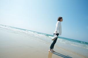 波打ち際で佇む女性の写真素材 [FYI04102537]