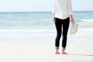 打ち寄せる波と靴を持った女性の写真素材 [FYI04102538]