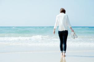 波打ち際を歩く女性の後ろ姿の写真素材 [FYI04102539]