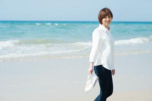 波打ち際で振り返って微笑む女性の写真素材 [FYI04102540]