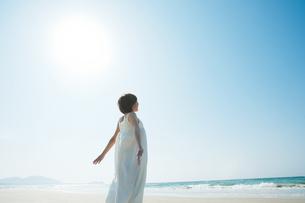 砂浜で空を見上げる女性の写真素材 [FYI04102543]