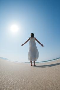 砂浜で空を見上げる女性の後ろ姿の写真素材 [FYI04102549]