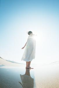 砂浜で空を見上げる女性の後ろ姿の写真素材 [FYI04102551]