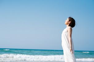 砂浜で光を浴びる女性の写真素材 [FYI04102554]