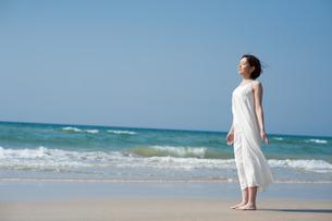 砂浜で光を浴びる女性の写真素材 [FYI04102556]