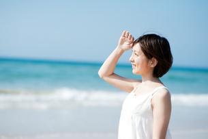 波打ち際で眩しそうにする女性の写真素材 [FYI04102565]