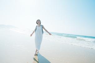 砂浜で空を見上げる女性の写真素材 [FYI04102567]