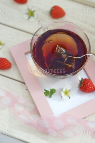 フォトフレームに置かれた紅茶といちごの写真素材 [FYI04102643]