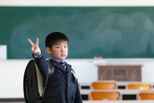 教室内でVサインをする新一年生の男の子の写真素材 [FYI04102914]