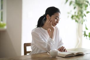 頬づえをついて読書する女性の写真素材 [FYI04103386]
