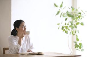 テーブルでカップを持って見上げる女性の写真素材 [FYI04103387]
