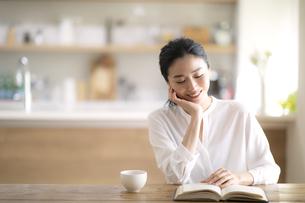 テーブルで読書をする女性の写真素材 [FYI04103388]
