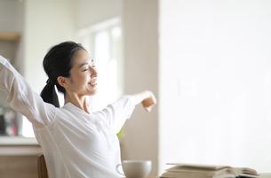 読書中に腕を広げて伸びをする女性の写真素材 [FYI04103390]