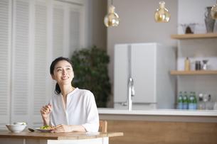 ダイニングキッチンで食事をしながら見上げる女性の写真素材 [FYI04103391]