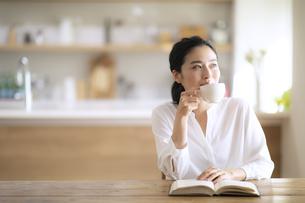テーブルでコーヒーを飲む女性の写真素材 [FYI04103392]