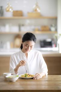 テーブルでパスタを食べる女性の写真素材 [FYI04103393]