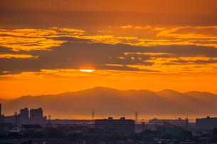 夕焼けの中、雲に隠れる太陽の写真素材 [FYI04103410]