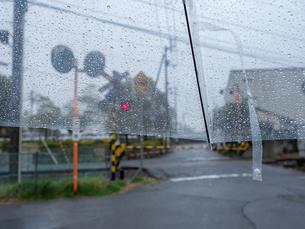 雨の日にビニール傘越しからみる町並み 踏切付近 雨粒の写真素材 [FYI04103571]