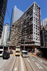 トランスフォーマーのロケ地にもなった香港島のモンスターマンション「海景樓」の前を走るトラムの写真素材 [FYI04103588]