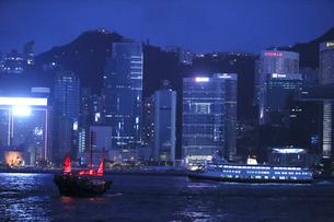 薄暮の香港・ビクトリア湾を航行する中国の昔のジャンク船を模した観光船「アクアルナ」(左)と離島行きのファーストフェリー(右)の写真素材 [FYI04103911]