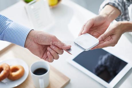 カフェで支払いをする男性の写真素材 [FYI04104859]