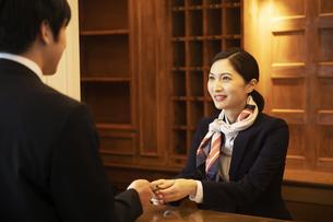 フロントで接客をするコンシェルジュの女性の写真素材 [FYI04106796]