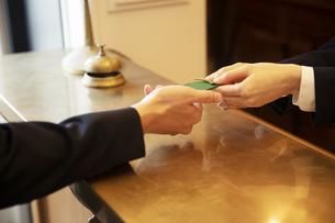 チェックインする男性の手元とフロントの女性の手元の写真素材 [FYI04106797]