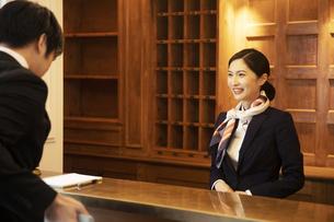 フロントで接客をするコンシェルジュの女性の写真素材 [FYI04106798]