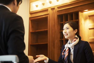 フロントで接客をするコンシェルジュの女性の写真素材 [FYI04106799]