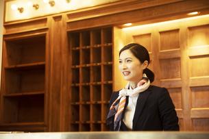 フロントで接客をするコンシェルジュの女性の写真素材 [FYI04106800]