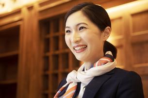 フロントで接客をする笑顔のコンシェルジュの女性の写真素材 [FYI04106803]