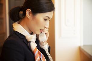 電話対応をするコンシェルジュの女性の写真素材 [FYI04106805]